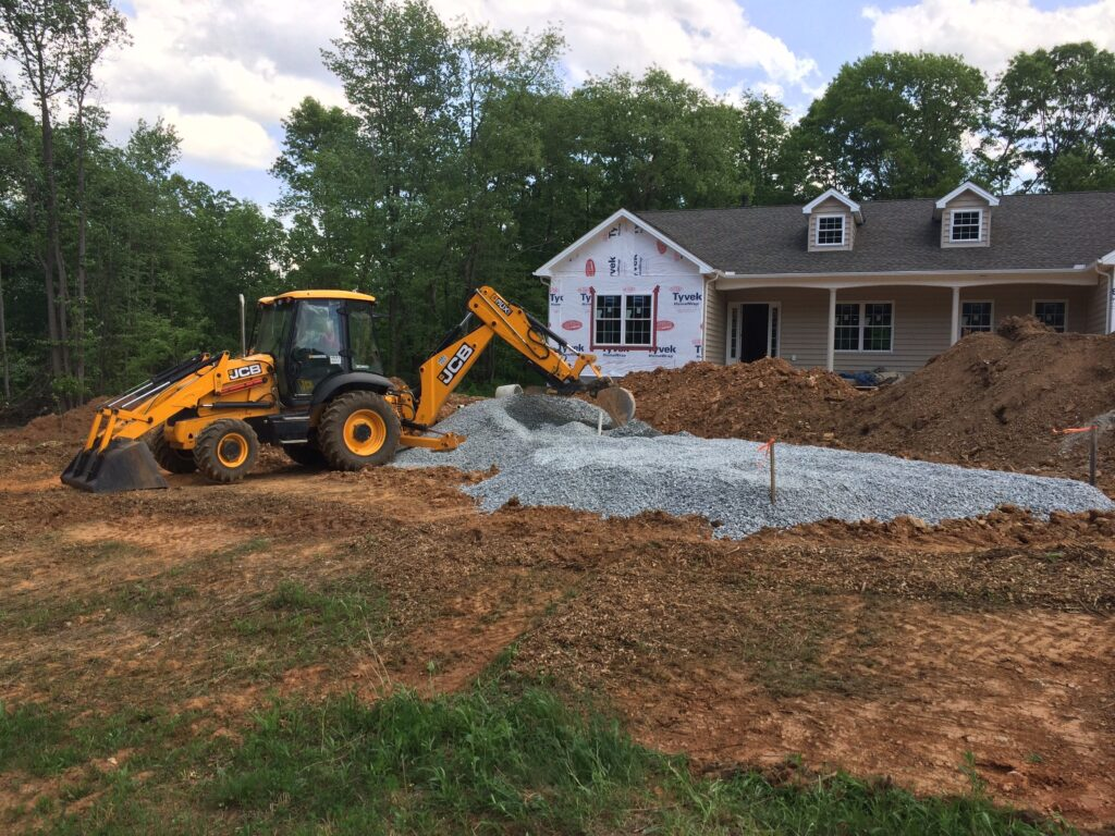 Backhoe Grading Stone for Septic System at Emory J. Peters Excavating and Paving Contractor, Inc.